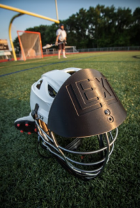Lacrosse shield to protect head against ball impact.